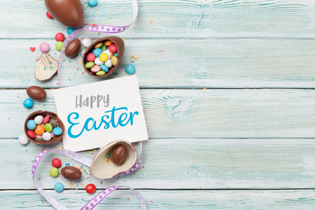 Easter greeting card with chocolate eggs and colorful candies. Top view on wooden table with space for your greetings