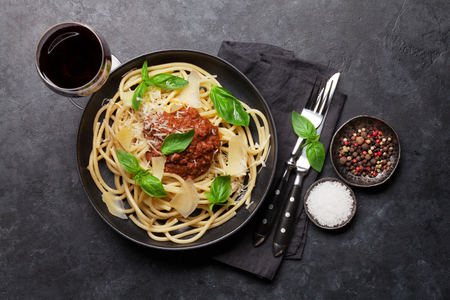 Spaghetti bolognese pasta with tomato and minced meat sauce, parmesan cheese and fresh basil. Red wine glass and cooking ingredients. Top view Фото со стока