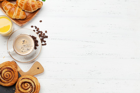 Coffee, croissants, orange juice, cinnamon rolls and berries breakfast. On wooden table. Top view with copy space for your text Stock Photo