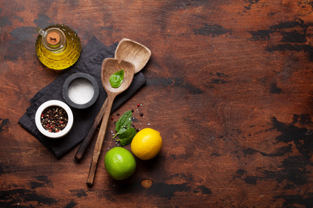 Cooking wooden utensils, condiments and spices on wooden kitchen table. Food cooking template concept. Top view with copy space for your text. Flat lay Archivio Fotografico