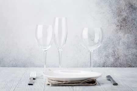 Dinner plate setting with cutlery and glasses. View with copy space