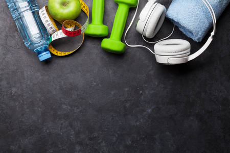 Fitness concept. Dumbbells, headphones and apple on stone background. Top view with space for your text