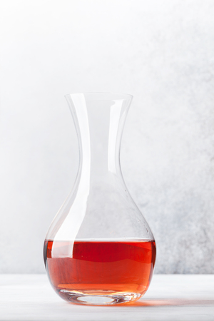 Rose wine in decanter on wooden table. In front of stone wall with space for your text