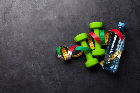 Fitness concept. Dumbbells, tape measure and water bottle on stone background. Top view with space for your text