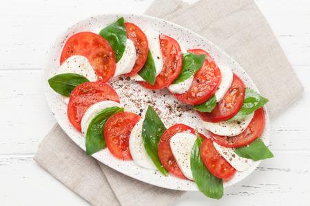 Delicious italian caprese salad with ripe tomatoes, fresh garden basil and mozzarella cheese. Top view flat lay Standard-Bild