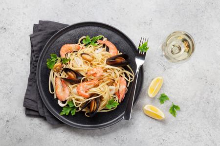 Spaghetti ai frutti di mare con vongole veraci e gamberi. Bicchiere da vino bianco. Vista dall'alto Archivio Fotografico