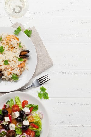 Delicious seafood risotto with shrimps, prawns, mussels. Dressed with parmesan cheese and parsley. And greek salad plate. Top view with copy space