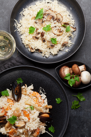 Delicious seafood risotto with shrimps, prawns, mussels and mushroom risotto. Dressed with parmesan cheese and parsley. Top view