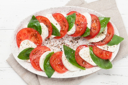 Delicious italian caprese salad with ripe tomatoes, fresh garden basil and mozzarella cheese. Top view flat lay Imagens