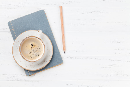 Coffee cup and notepad on wooden table. Top view with space for your ideas