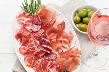 Traditional spanish jamon, prosciutto crudo, italian salami, parma ham. Antipasto plate and glass of wine