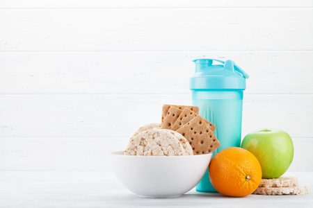 Fitness and healthy food concept. Fruits, granola and drink bottle on wooden table. With copy space for your text