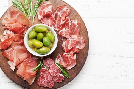 Traditional spanish jamon, prosciutto crudo, italian salami, parma ham. Antipasto plate and olives. Top view flat lay. With copy space Reklamní fotografie