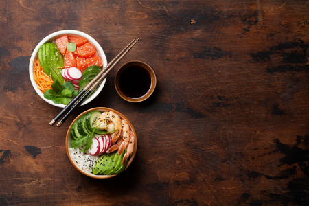Poke bowl with salmon, shrimps and vegetables. Traditional Hawaiian raw fish salad. Top view with copy space