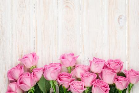 Roze rozen over houten tafel. Bovenaanzicht met kopieerruimte voor uw tekst