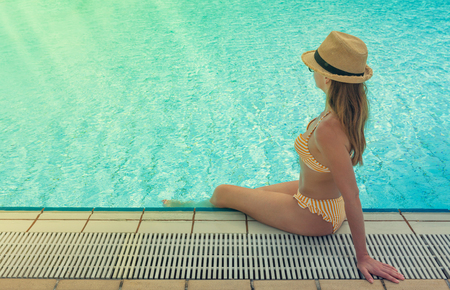 Young woman relaxing in swimming pool. With copy space for your text. Sunny toned