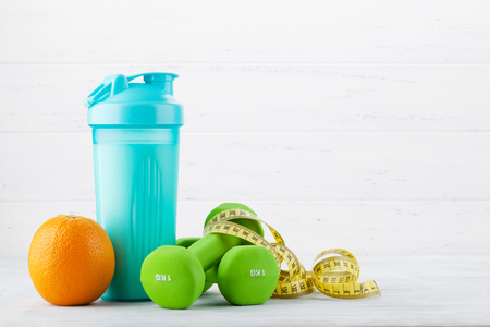 Fitness and healthy food concept. Dumbbells, fruits and drink bottle on wooden table. With copy space for your text Stock Photo