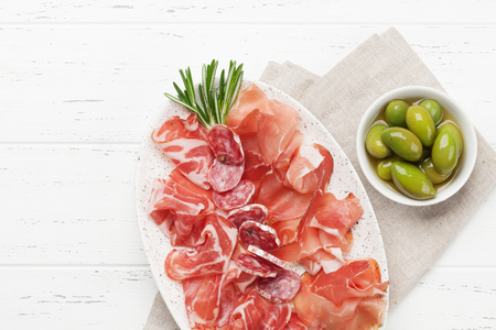 Traditional spanish jamon, prosciutto crudo, italian salami, parma ham. Antipasto plate and olives. Top view flat lay. With copy space Archivio Fotografico