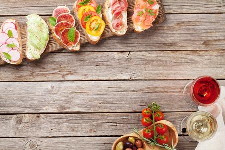 Brushetta oder traditionelle spanische Tapas. Vorspeisen italienische Antipasti-Snacks auf Holzbrett mit Rose und Weißwein. Draufsicht und flach liegen mit Platz für Ihren Text