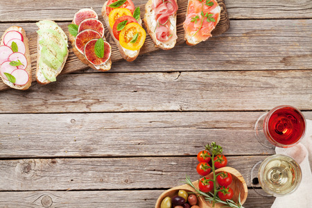Brushetta or traditional spanish tapas. Appetizers italian antipasti snacks set on wooden board with rose and white wine. Top view and flat lay with space for your text