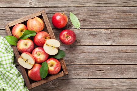 Manzanas rojas maduras en mesa de madera. Vista superior con espacio para su texto