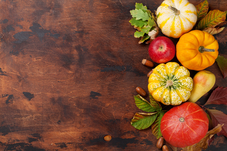Autumn backdrop with pumpkins, apples, pears and colorful leaves over wooden background. Top view with space for your text