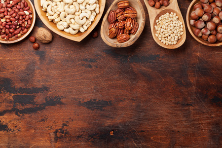 Various nuts selection: peanuts, hazelnuts, chestnuts, walnuts, pistachio and pecans on wooden table. Top view with space for your text