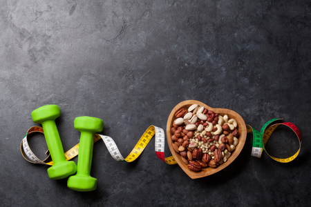 Healthy food and fitness concept. Nuts and dumbbels. Top view flat lay with copy space for your text