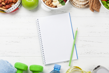 Healthy food and fitness concept. Various nuts, cereal, salad and dumbbels. Top view flat lay with notepad for your text