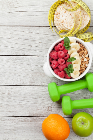 Healthy food and fitness concept. Breakfast cereal, fruits, nuts and sport equipment. Top view flat lay with copy space for your text