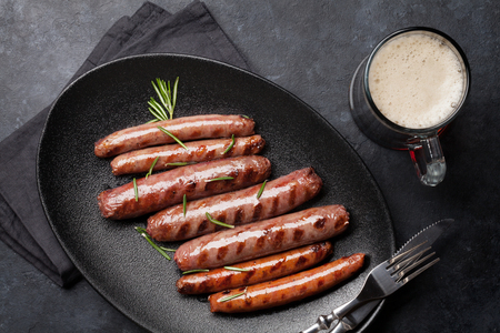 Grilled sausages with rosemary herbs and glass of dark beer. Top view