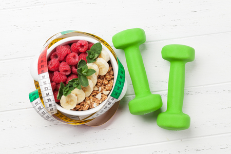 Healthy food and fitness concept. Breakfast cereal and sport equipment. Top view flat lay