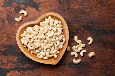 Cashew nuts on wooden table. Top view with space for your text