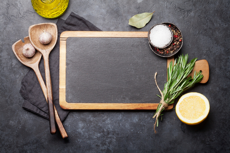 Cooking ingredients and utensils on stone table. Top view with chalkboard for your recipe