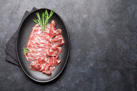 Traditional spanish jamon, prosciutto crudo, italian salami, parma ham. Antipasto plate. Top view flat lay. With copy space