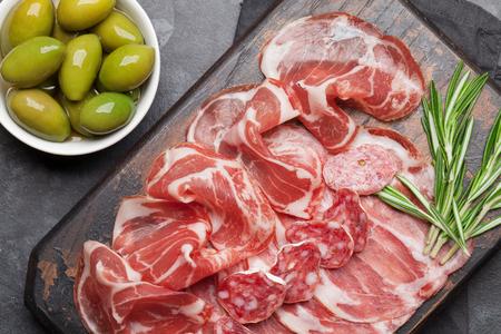 Traditional spanish jamon, prosciutto crudo, italian salami, parma ham. Antipasto plate and olives. Top view