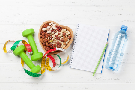 Healthy food and fitness concept. Various nuts and dumbbels. Top view flat lay with notepad for your text