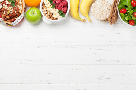 Healthy food and fitness concept. Salad, fruits, vegetables, nuts and breakfast cereal. Top view flat lay with copy space for your text