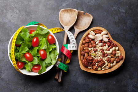 Healthy food and fitness concept. Salad, fruits, vegetables, nuts and breakfast cereal. Top view flat lay