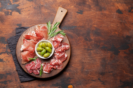 Traditional spanish jamon, prosciutto crudo, italian salami, parma ham. Antipasto plate and olives. Top view flat lay. With copy space Stock Photo