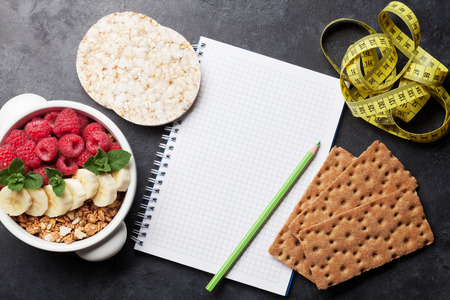 Healthy food and fitness concept. Breakfast cereal and notepad. Top view flat lay with copy space for your text