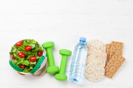 Healthy food and fitness concept. Breakfast cereal, salad and sport equipment. Top view flat lay with copy space for your text Stock Photo