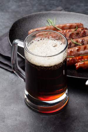 Glass of dark beer and grilled sausages with rosemary herbs