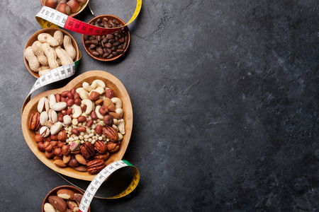 Various nuts selection: peanuts, hazelnuts, chestnuts, walnuts, pistachio and pecans on stone table. Top view with space for your text