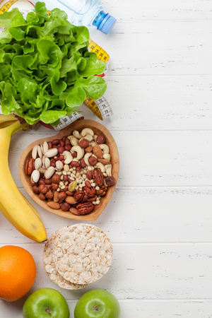 Healthy food and fitness concept. Various nuts, fruits, cereal and salad. Top view flat lay with copy space for your text