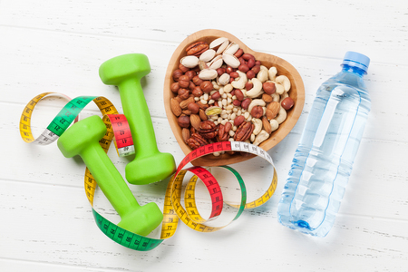 Healthy food and fitness concept. Various nuts and dumbbels. Top view flat lay
