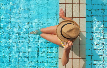Young attractive woman relaxing in swimming pool. Top view with copy space for your text