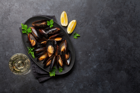 Delicious cooked seafood mussels with tomato sauce, parsley and lemon. And glass of white wine. Top view with space for your text. Stock Photo