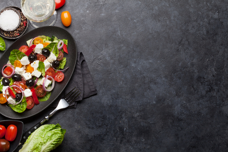 Greek salad with cucumber, tomato, pepper, lettuce, onion, feta cheese and olives, dressed with olive oil. Top view with white wine glass and space for your text Stock Photo