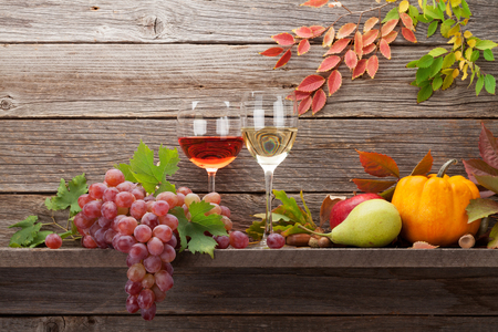Autumn still life card with pumpkins, grapes, apples, pears, wine and colorful leaves in front of wooden wall. With space for your text